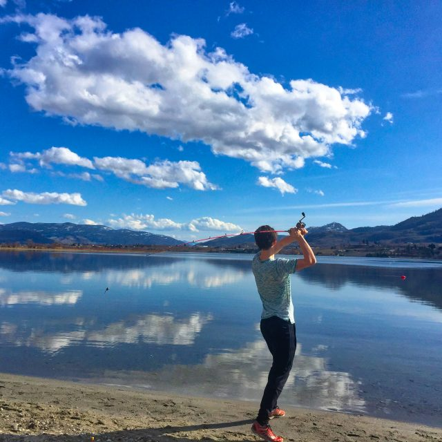 Boy fishing at Osoyoos Lake in front of the Beach House Osoyoos vacation rental